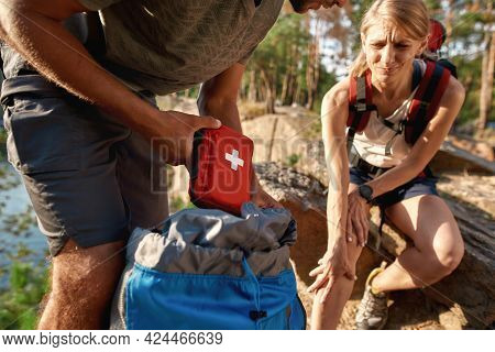 Young Caucasian Man Using First Aid Kit On Injured Woman Sitting On Rock During Hiking In Summer Nat