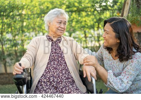 Help And Care Asian Senior Or Elderly Old Lady Woman Patient Sitting On Wheelchair At Park In Nursin