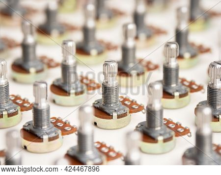 Electronic parts aligned. Many potention meters or variable resistors  (also called volume pots) aligned on neutral white background.