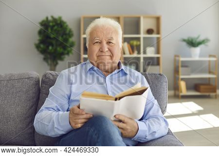 Smiling Elderly Man Or Grandfather In Blue Shirt Sitting On Sofa And Reading Book At Home