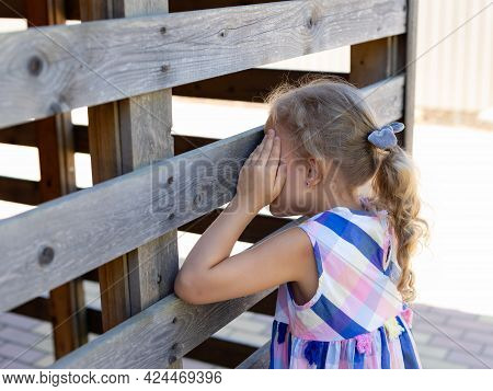 Cute Little Girl Covering Her Eyes With Hands, Playing Hide And Seek Standing Near Wooden Fence. Out
