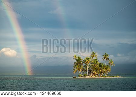 Tiny Tropical, Uninhabited Island In The Sea With Palm Trees And Rainbow On The Cloudy Sky. Vacation