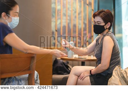 Two Female Friends With Spray Their Hands With Antiseptic Spray In Cafe