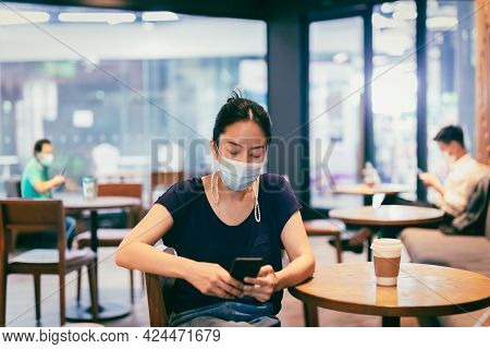 Asian Woman Wearing Medical Mask Using Cell Phone Sitting At Table In Cafe