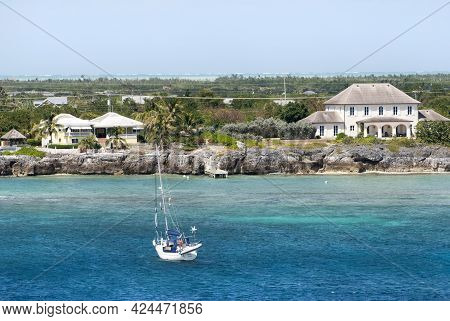 The View Of A Drifting Yacht Near Grand Cayman Island With Residential Houses In A Background (cayma