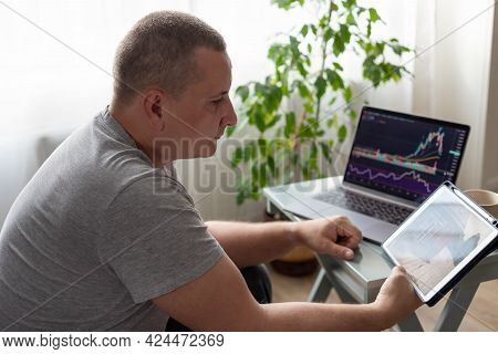 Man Looking At Home Security Camera On Digital Tablet. Home Security System. Freelance Concept. Blur