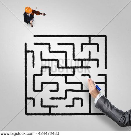 Top View Of Businesswoman Playing Violin And Drawn Labyrinth On Floor