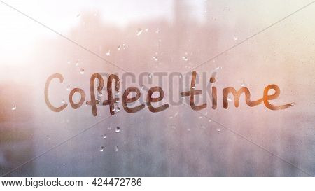 Handwritten Text Coffe Time On Misted Glass On Blue Window With Orange Sunset Flooded With Raindrops