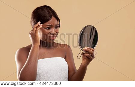 Sad Black Woman Looking To Mirror And Touching Face Suffering Skin Problems