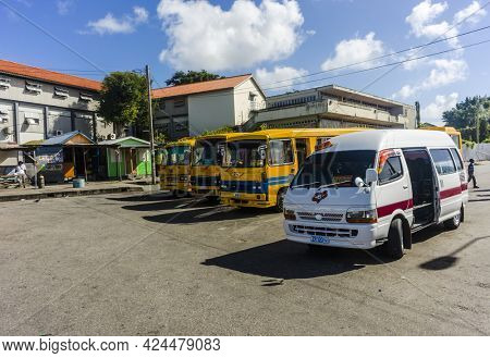 BRIDGETOWN, BARBADOS - DECEMBER 17, 2013: Various yellow buses and a minibus standing at Constitution River Terminal in Barbadian capital city Bridgetown. White private taxi-bus vehicles are called ZR