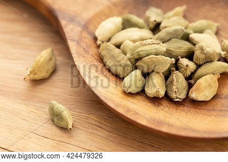 Cardamom On Wooden Spoon. Cooking Spices. Elettaria Cardamomum