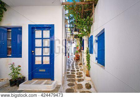 Beautiful Traditional Narrow Alleyways Of Greek Island Towns. White Houses, Flower Pots, Blue Window