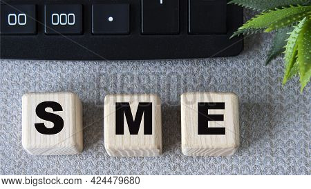 Sme (subject Matter Expert) - Acronym On Wooden Cubes On A Gray Background With A Calculator. Busine