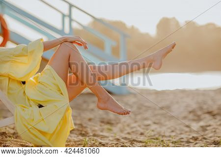 Woman's Long Slim Legs On The Sand Beach While Sunset. Copy Space.