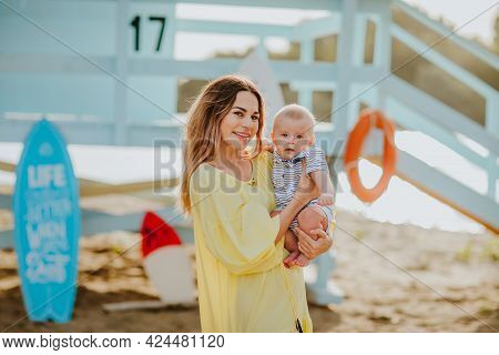 Beautiful Young Woman In Summer Yellow Dress Posing With Her Newborn Boy On The Beach Against Blue L