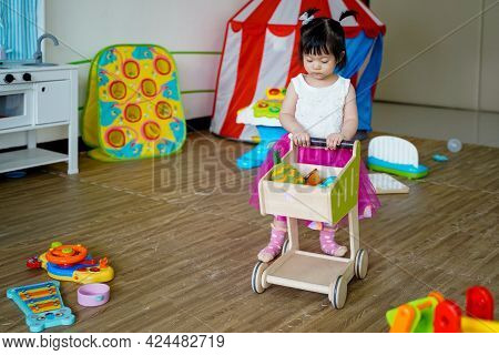 Asian Baby Girl Playing With Cart Toys In Playroom With At School No Teacher Care.