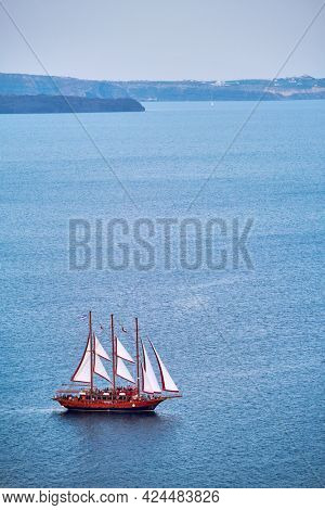 Tourist schooner vessel ship boat in Aegean sea near Santorini island with tourists going to sunset viewpoint. Santorini, Greece