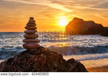 Cairn stack of stones pebbles cairn on the beach coast of the seaon sunset. Agios Ioannis beach, Milos island, Greece