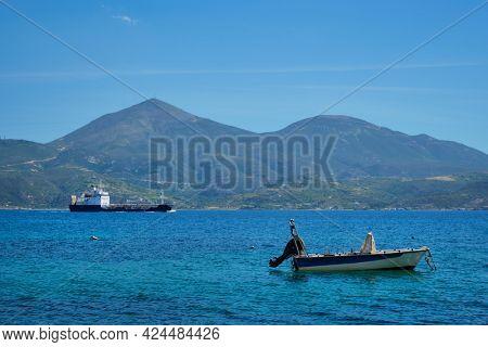 Greek fishing speed boat and cargo ship in the Aegean sea, Milos island, Greece
