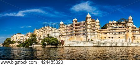 Panorama of famous romantic luxury Rajasthan indian tourist landmark - Udaipur City Palace on sunset with cloudy sky - surface level view. Udaipur, Rajasthan, India
