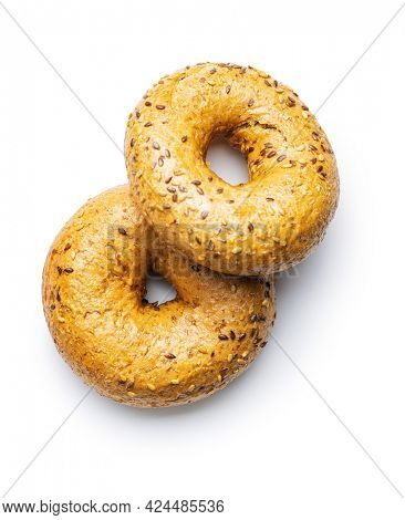 Whole grain baked bagel isolated on white background.