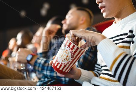 Friends Are Watching A Movie In The Cinema With Popcorn. People Sit In The Armchairs Of The Cinema A