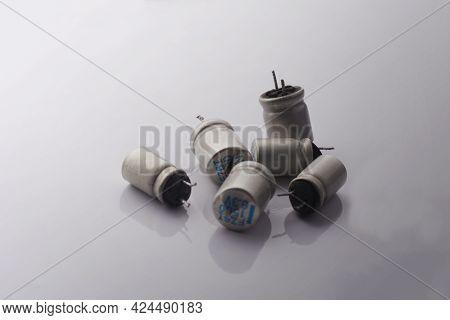 Damaged Cracked Electrolytic Bloated Exploded Capacitor On White Background. Minimal Repair Electoni