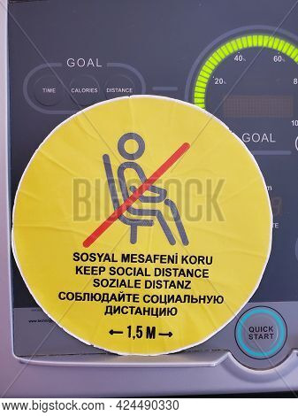Yellow Sticker Warning About Keeping Social Distance In Turkish, English, German, Russian Languages.