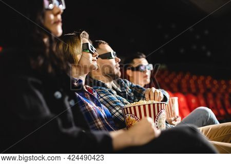 Friends Are Watching A Movie In The Cinema. People Sit In The Armchairs Of The Cinema And Look At Th
