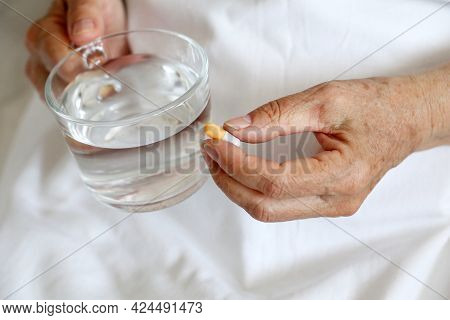 Elderly Woman With Pill And Glass Of Clean Water In Wrinkled Hands. Medication In Capsule, Taking Se
