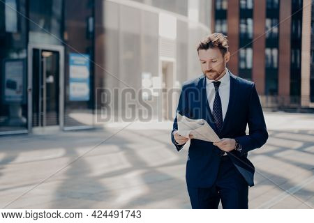 Successful Handsome Young Businessman With Neat Beard In Formal Wear Reads Newspaper While Walking B