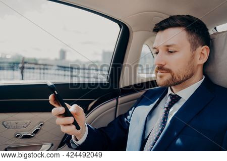 Male Bearded Investor In Blue Suit Checking Phone Messages And Notifications, Receiving Troubling Ne