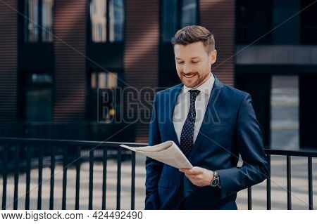 Good News. Young Rich Progressive Firm Owner Reading Newspaper With Smile While Standing In Front Of