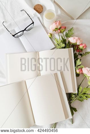 Opened Books And Flowers Top View On White Bed. Mock Up Design