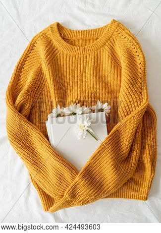 Top View Of A Book With White Chrysanthemum Flowers On Yellow Sweater