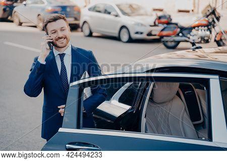 Confident Smiling Executive Dressed In Blue Formal Suit Leaving Black Limousine After Arriving At Hi