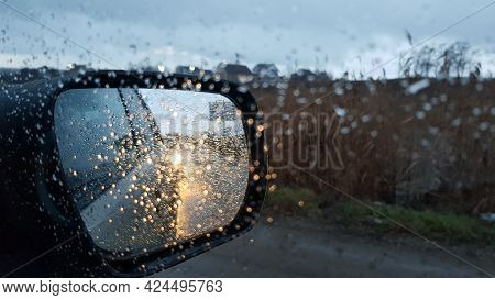 Wet Glass Texture With Raindrops Rolling On Window. Car Side View Mirror With Defocused Reflections