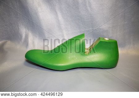 Shoe Block For Molding The Top Of Shoes In Green Color On A Background Of Genuine Leather In Blue Co