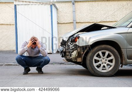 Young Man Driver In Car Accident Holding His Head Near Broken Car On The Road After Car Accident. Ca