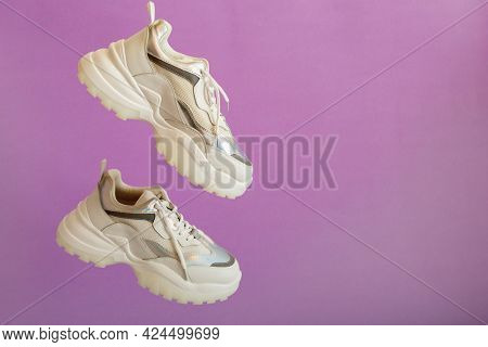Urban White Neon Sneakers Fly On Color Purple Background With Copy Space. White Sport Sneakers Shoes