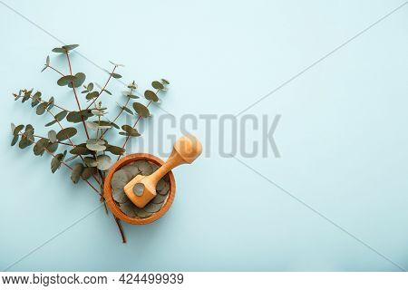 Eucalyptus Branches And Wooden Mortar On Colored Blue Background With Copy Space. Eucalyptus Herbal
