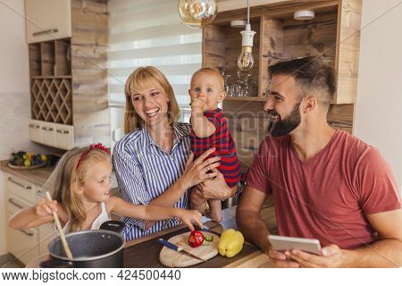 Beautiful Happy Family Having Fun Cooking Lunch Together, Sitting At Kitchen Counter And Enjoying Le