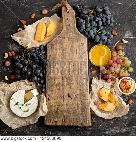 Empty Wooden Vintage Cutting Board In Center Of Frame Made Of Honey Grapes Cheese Snack Other Ingred