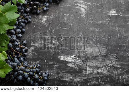 Black Juicy Grapes On Vintage Dark Concrete Background. Frame Made Of Grapes. Copy Space For Text Or