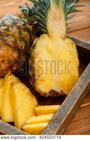Sliced Pineapple. Bromelain Tropical Summer Fruit Pineapple Halves And Whole Pineapple On Brown Dark