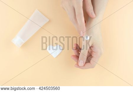 Moisturizer On A Woman's Hand. Women's Hands, Cream In The Shape Of A Heart And A Tube For Cream On