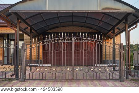 Automatic Wrought Gates In Black And A Canopy Before Garage