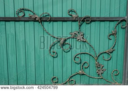 Black Green Texture Of Iron Forged Rods In The Pattern On The Metal Wall Of The Fence