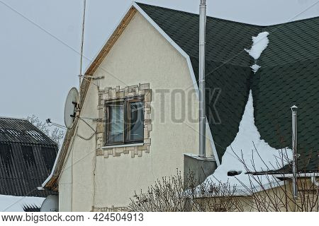 Attic Of A Gray Concrete House With A Window With A Green Tiled Roof And A Chimney Under White Snow