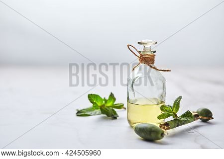 Bottle Of Essential Oil Of Mint And Green Leaves And Jade Massage Roller For The Face. Natural Organ